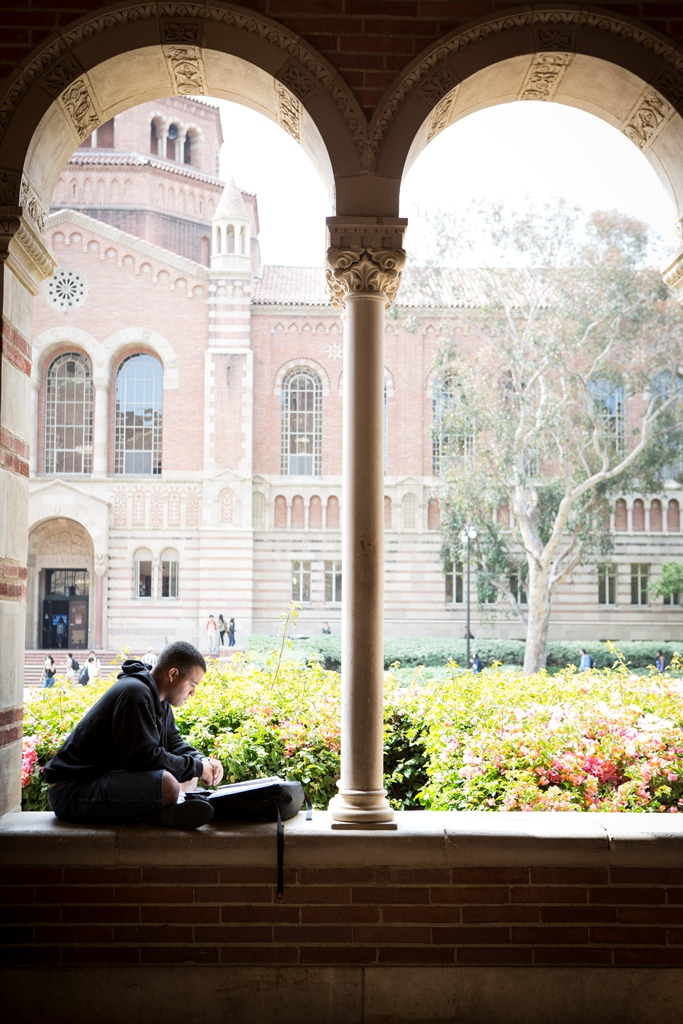 Student reading in Royce Hall portico