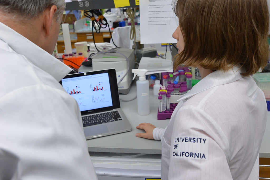 Student showing data to professor on laptop at lab bench